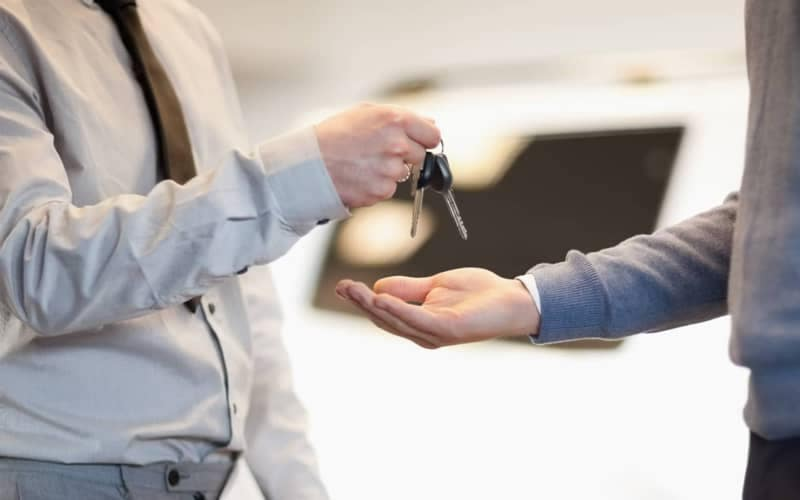 Person handing other person car keys