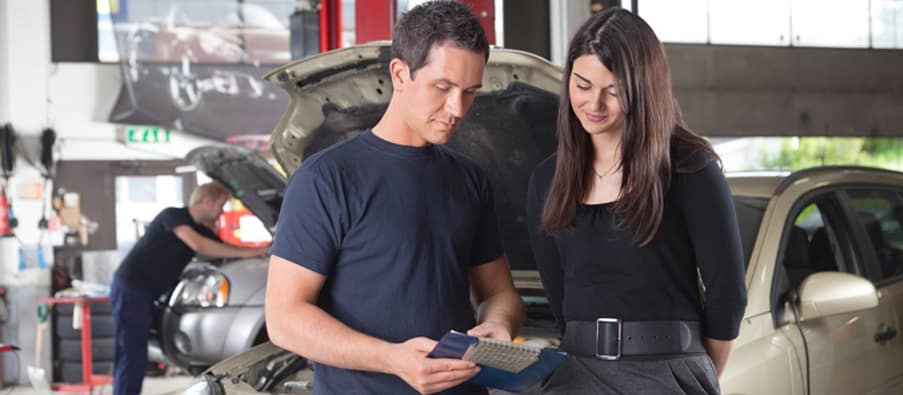 trained mechanic reviewing order with customer