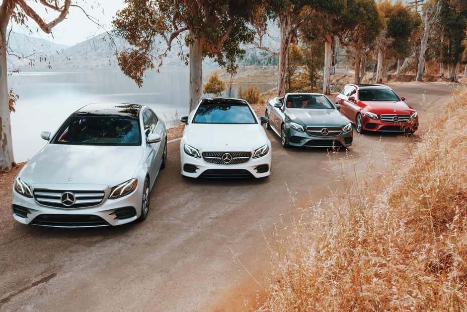 Image of four different 2019 Mercedes E-Class sedans parked on a dirt road near a lake.