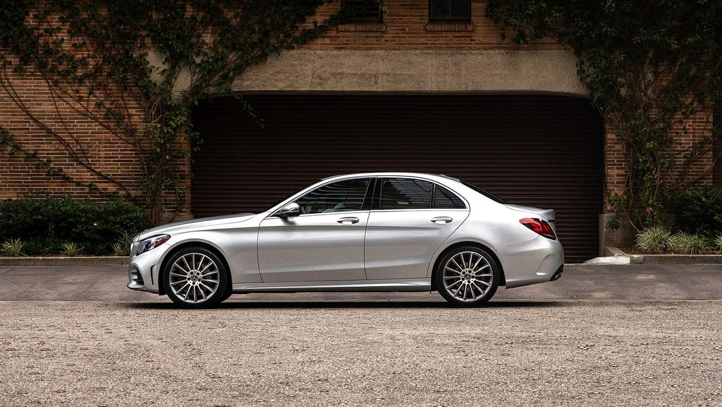 Side Image of a silver 2019 Mercedes-Benz C-Class sedan parked by some trees.