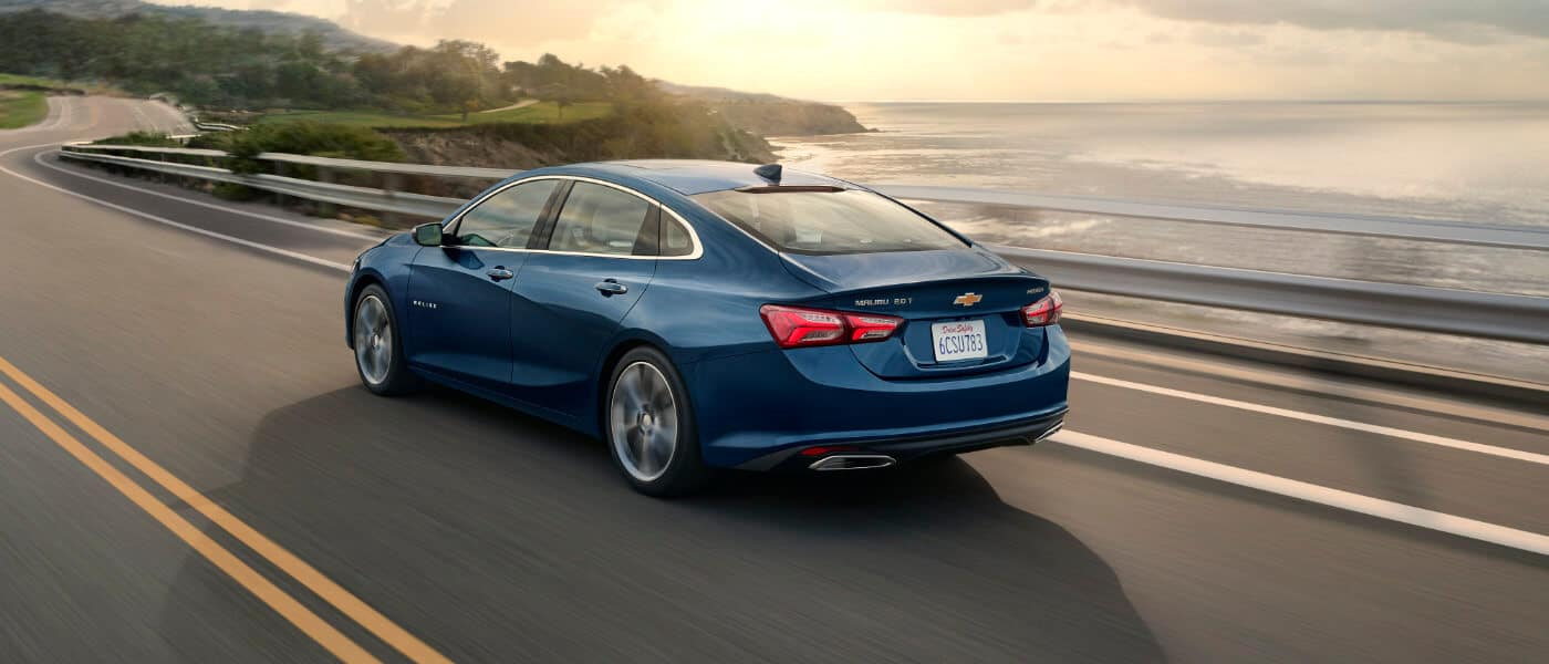 2020 blue Chevy Malibu driving on ocean side highway