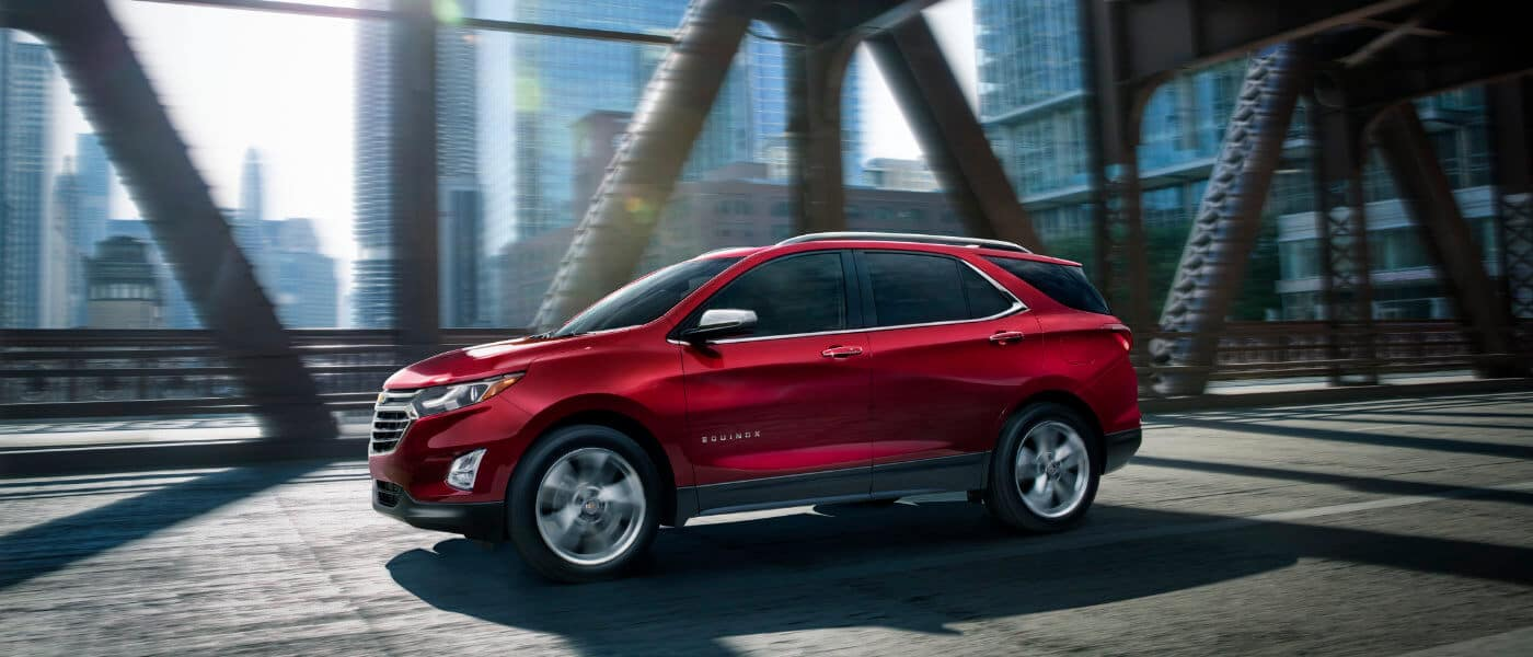 2020 Chevy Equinox in Red Exterior Driving on City Bridge