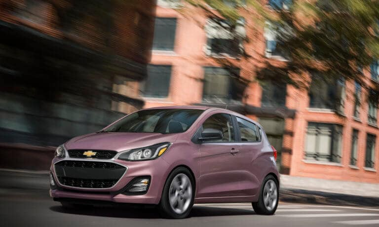 2020 Chevy Spark in pink driving throughout city