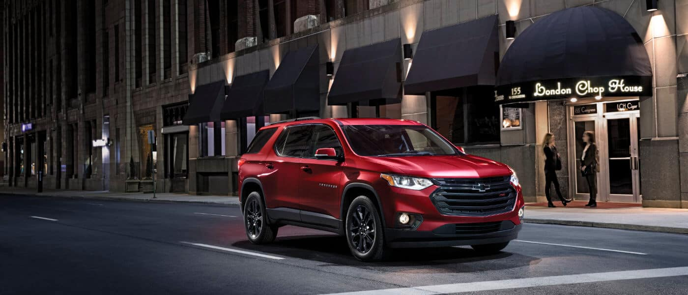 2020 Chevy Traverse in red driving thoughout the city at night
