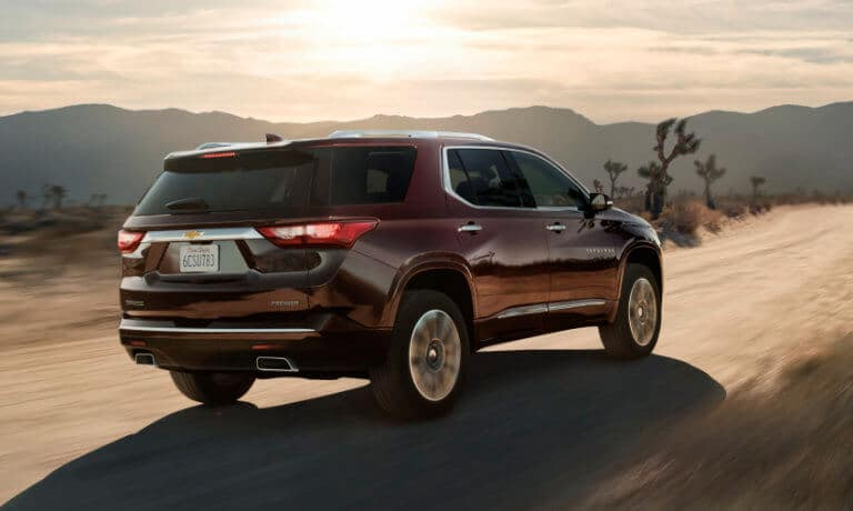 2020 Chevy Traverse in red back view driving throughout Desert