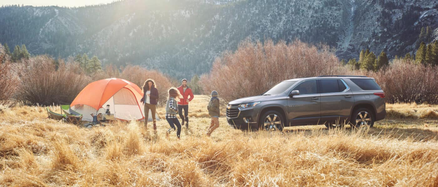 2020 Chevy Traverse parked at camp site in the mountians with family camping