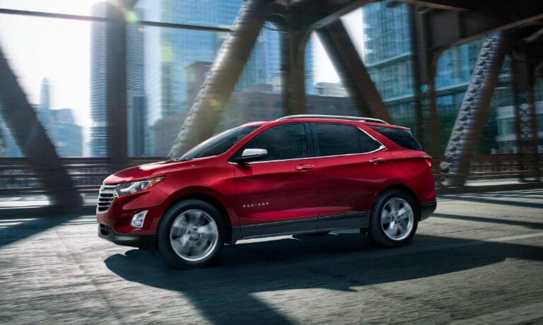 2020 Chevy Equinox in red driving over bridge in the city