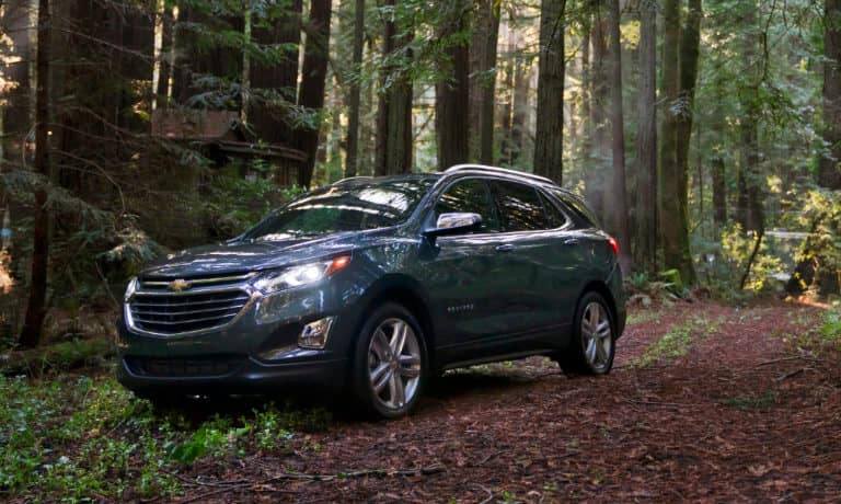 2020 Chevy Equinox in blue Driving off road throughout a forest