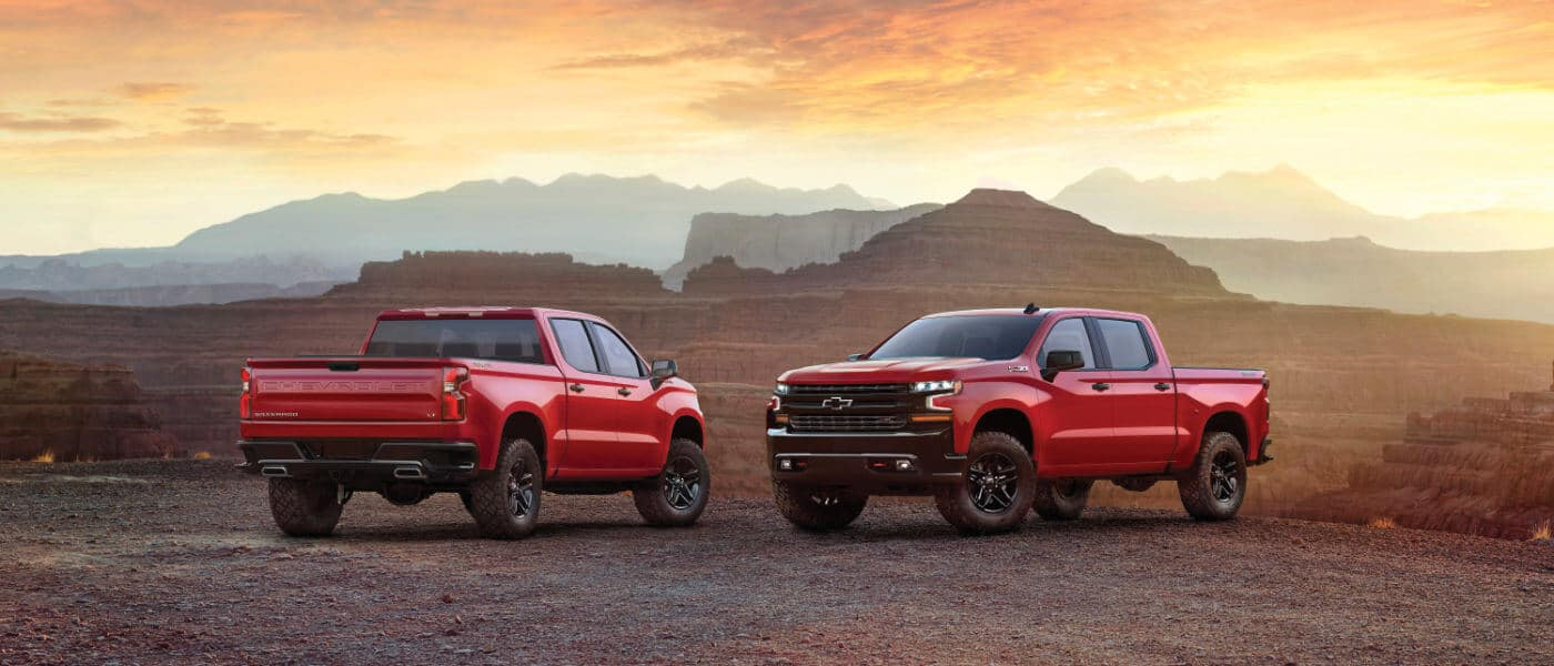 2020 Chevy Silverado in red showing two one parked showing the front and the other showing the back parked off road in desert mountians