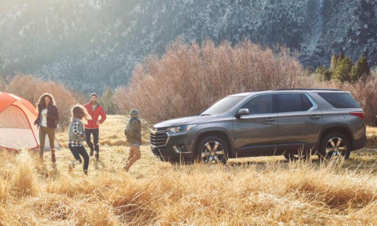 2020 Chevy Traverse in gray parked at camp site in the mountians with a family