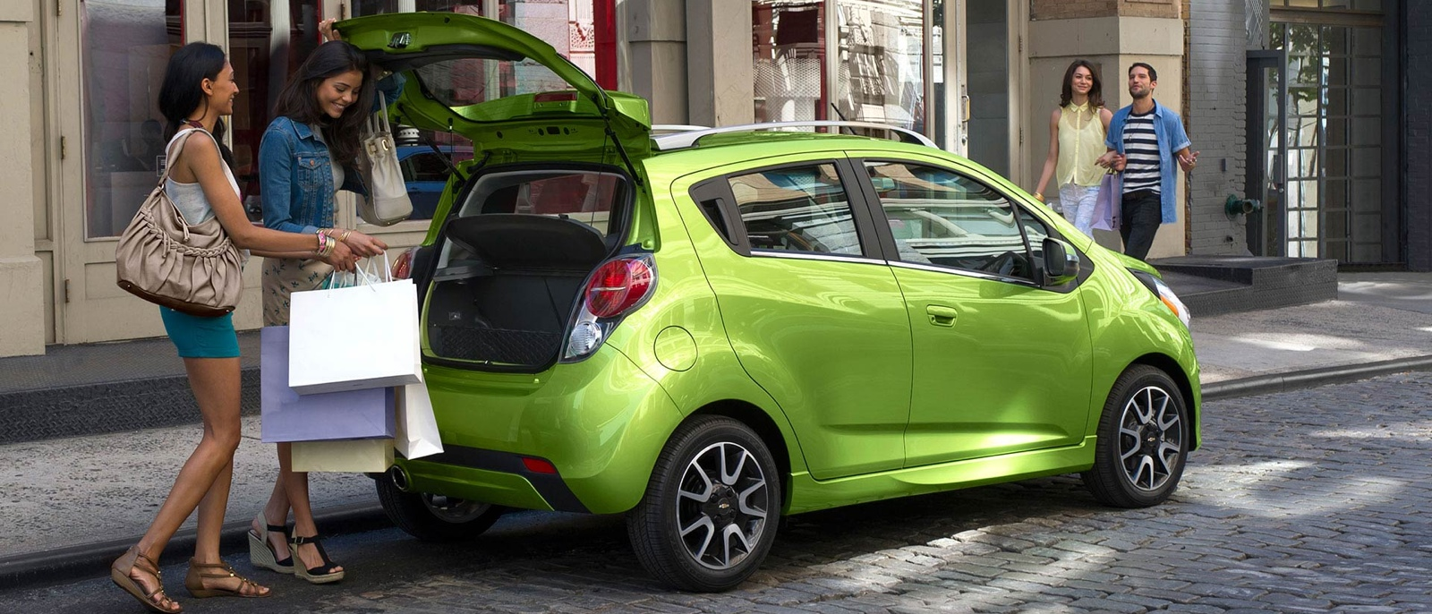 Women putting shopping bags in trunk of 2015 Chevrolet Spark