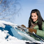 Winter car - woman remove snow from windshield with snow brush