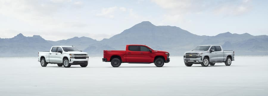 three 2019 Chevy Silverado's parked near a mountainside