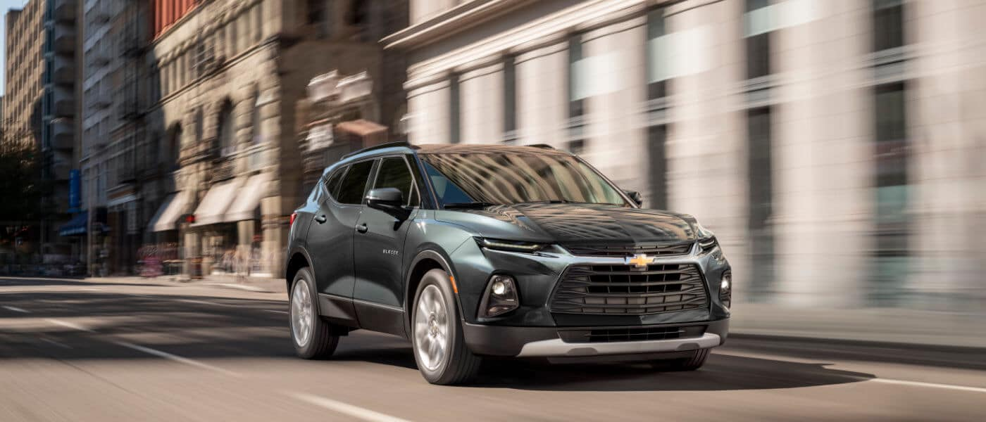 2020 Chevy blazer in green driving throughout a city durring the day