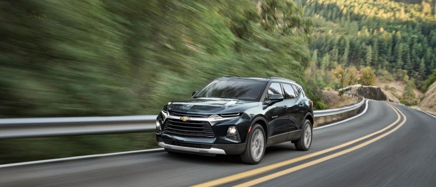 2020 Chevy Blazer in blue Driving Down Forest Highway
