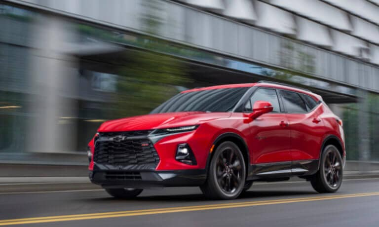 2020 chevy blazer in red driving on street in motion past a corporate building
