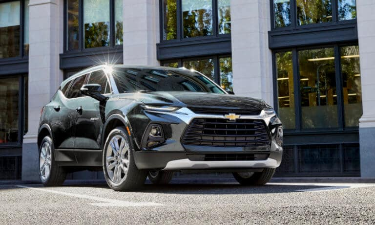 2020 chevy blazer in green parked infront of building with sun shinning on the vehicle