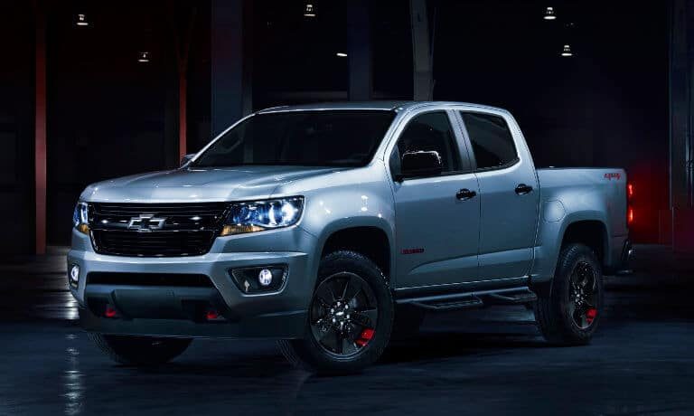 2020 Chevy Colorado in silver parked in a dark room with red lights