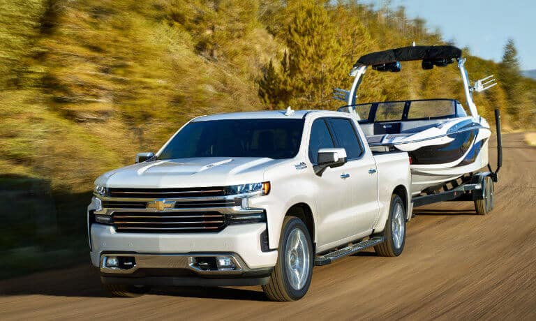 2020 chevy silverado in wihte driving on highway towing a boat