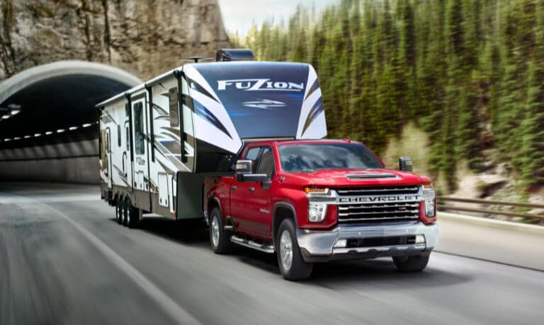 2020 chevy silverado 2500 in red driving while towing a tralier