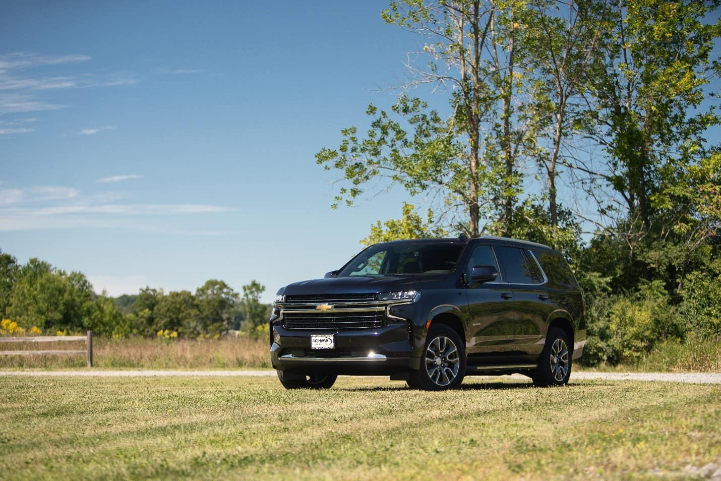new black 2021 Chevy Tahoe parked in an open field with trees in the background