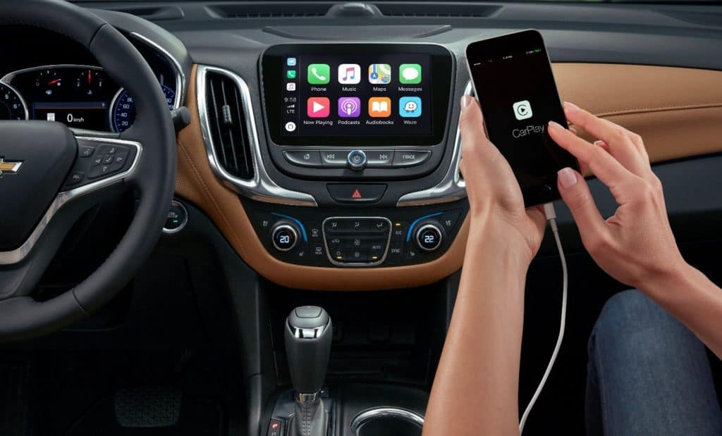 interior of a 2020 Chevy Equinox with two-tone black and brown leather accents, touchscreen infotainment center, and an Apple phone plugged connected