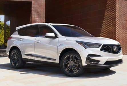 White 2020 Acura RDX parked next to a boxy brown building