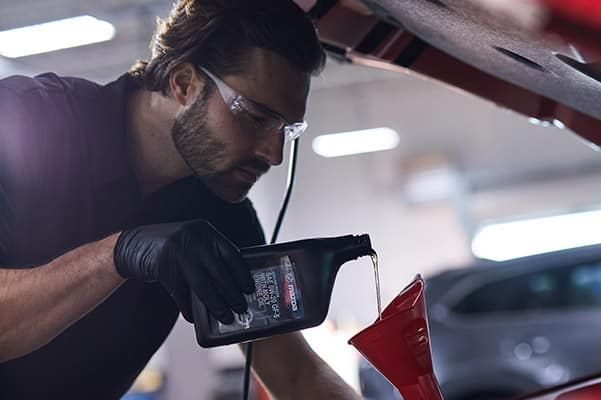 Mazda service person performing an oil change