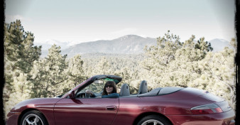Roxanne sitting in her Porsche 911 Cabriolet, parked on the shoulder of a mountain road.