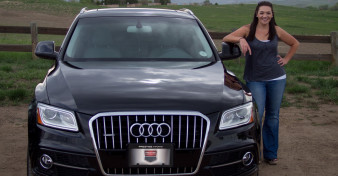 One of Prestige Imports' many satisfied customers stands with her Audi Q5 in front of open space and mountains