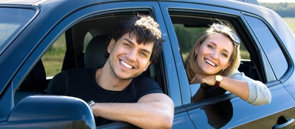 2 people with heads out car window