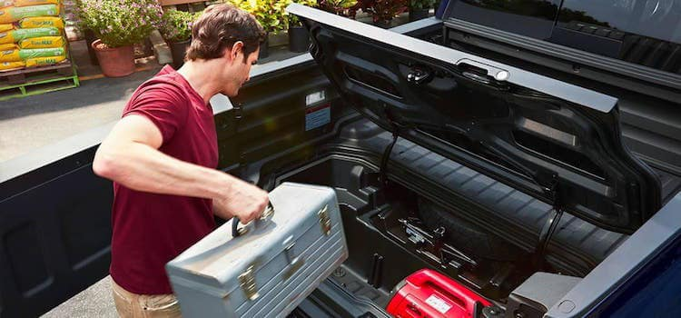 Man Loading Toolbox Into Honda Ridgeline Truck Bed