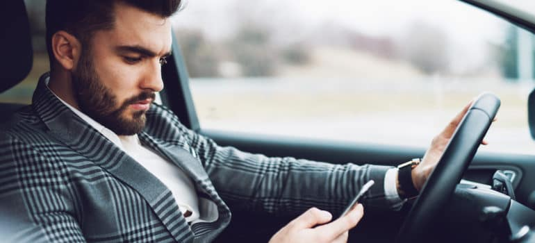 Man holding phone while in driver's seat