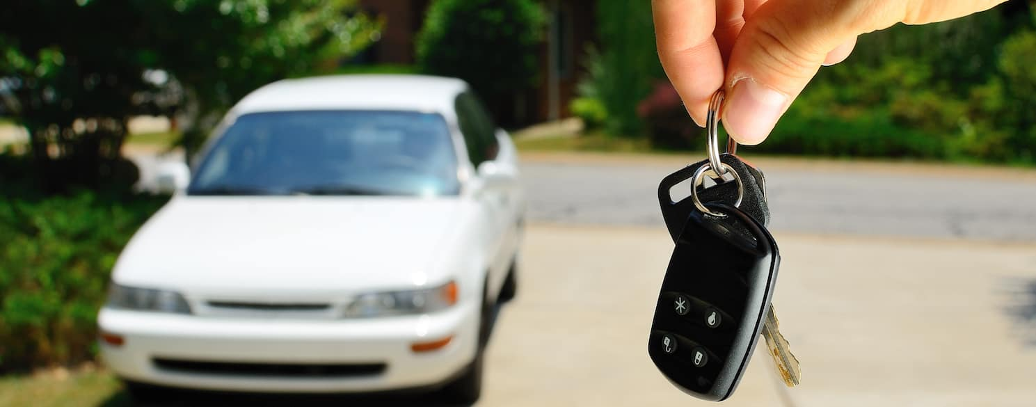 Fingers holding car keys with white car in background