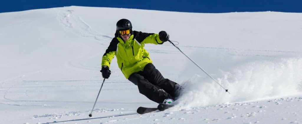 Skier skiing downhill, blue sky on background